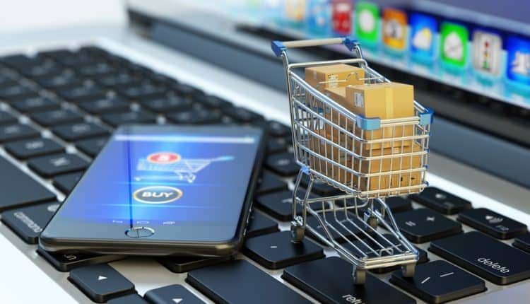Online shopping, internet purchases and e-commerce concept, modern mobile phone with buy button on the screen and shopping cart full of package boxes on computer laptop keyboard