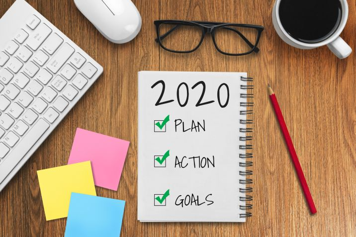 New Year Resolution Goal List 2020 – Business office desk with notebook written in handwriting about plan listing of new year goals and resolutions setting.